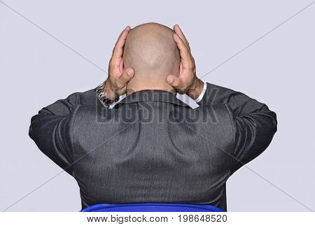 Rear view from a worried bald head businessman holding is head and ears.
