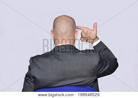 Rear view from a depressed businessman point head with gun hand.