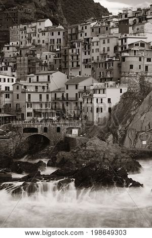 Manarola overlook Mediterranean Sea with buildings over cliff in Cinque Terre, Italy in black and white