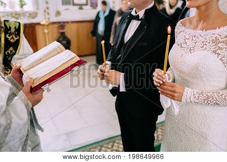 Unrecognizable Bride And Groom In The Church During The Christian Wedding Ceremony. Hands Of A Pries