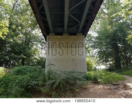 cement support column underneath a wooden covered bridge