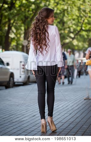Portrait Of A Beautiful Young Girl Outdoors In The City, Standing In Clothes