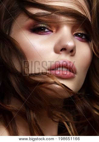 Close up portrait of beautiful young model with evening makeup, perfect skin, wavy hair. Trendy colorful smoky eyes.