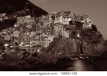 Manarola overlook Mediterranean Sea with buildings over cliff black and white in Cinque Terre at night, Italy.