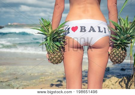 Sexy tropical woman butt close up with exotic pineapple fruit on the beach of paradise island of Bali. Healthy diet concept. I love Bali.