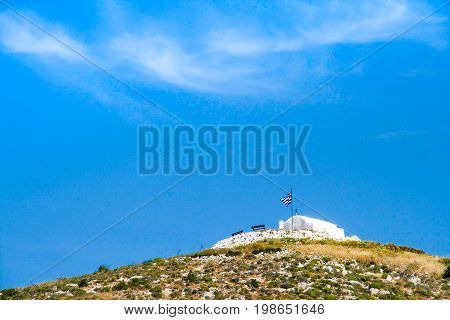 Low angle view on small chapel standing on hill in greek island under a blue sky and some clouds above it. Cyclades islands