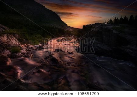 Colorful sunrise over the rapids of Swiftcurrent Creek in Glacier National Park Montana