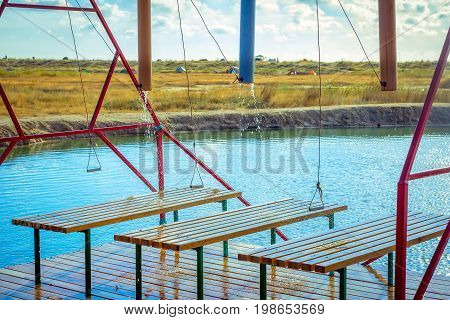 Outdoors water massage shower equipment. Self directing pressure cascade douche for spa procedures on a hot pond coast. Recreation and hydrotherapy device.