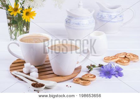 Medicinal plant chicory, Diet drink chicory in a cup with milk for breakfast on a white table.