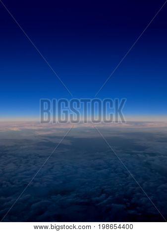 Flying high.  Abstract art, fluffy clouds swirl below a vivid blue evening skyline high above earth.