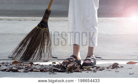 Old Woman Is Sweeping Dry Leaf.