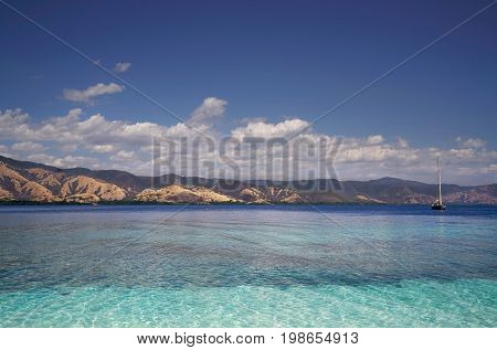 Boat Sailing On Clear Blue Tropical Ocean Water During The Day With Broad Green Island Behind, Flore