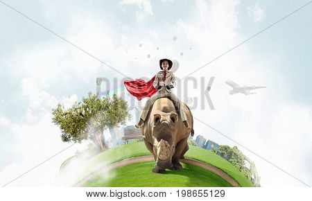Businesswoman riding rhino. Mixed media