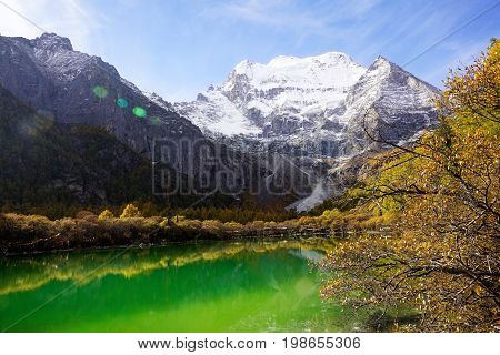 Shangri La, Green Clear Colored Pearl Lake With Holy Snow-clad Mountain Chenrezig And Yellow Orange