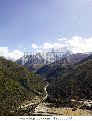 Shangri La, Holy Snow-clad Mountain Chanadorje And Green Pine Trees With A Road Going In Between Tow