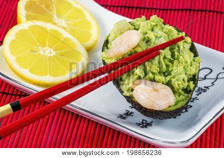 Tasty avocado salad with shrimps, lemon and red chopsticks on the white plate