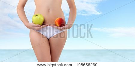 woman holding fruits with hands near waistline isolated on blue summer sea and sky background body care diet concept