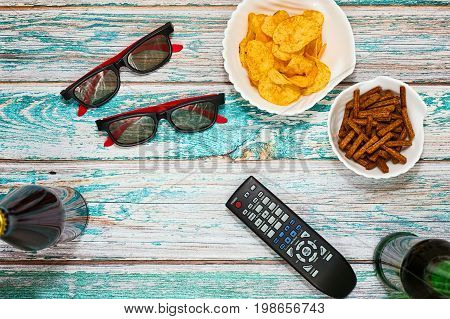 Home party for couple flatlay concept - beer salted snacks. remote control and TV glasses on grungy table in top view