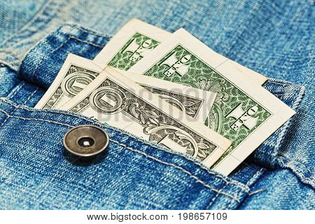 A few bucks in old faded jeans jacket pocket - close up caption with soft focus