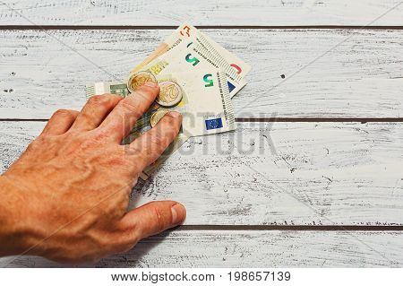 Payout or bet concept - male hand puts euro bank notes and coins on scratched wooden table