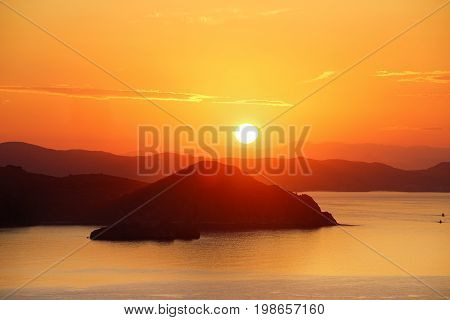 Orange sunrise view from Padar Island part of komodo national park with little silhouette boats in the ocean Flores Indonesia.