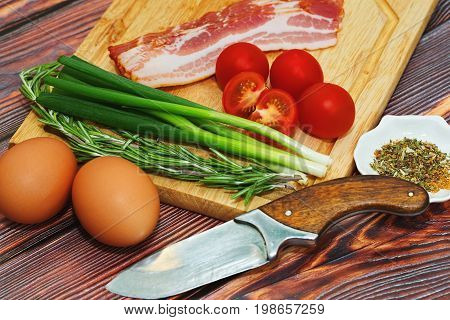 Some ingredients for nutritious meal cooking - eggs pork bacon tomatoes green onion and rosemary - close up caption in simple rural style