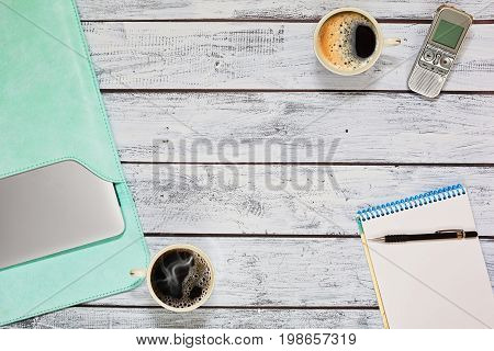 Interviewing during coffee break - two coffee cups dictaphone laptop and blank notebook on wooden table