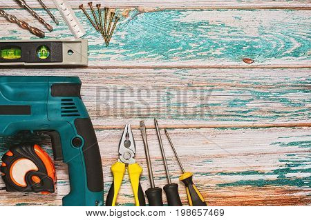 Different hand tools such as screwdrivers and pliers and hand perforator with drillers and screws measuring tools on rough table - top view