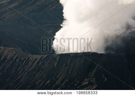 Tourists Watching White Smoke Coming Out Of The Active Volcano Crater Mount Bromo From Nearby At The