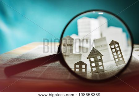 Magnifying glass in front of an open newspaper with paper houses. Concept of rent search purchase real estate.