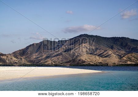 Empty White Sand Beach With Blue Ocean During The Day Overlooking Mountain Landscape With Green Vege