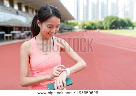 Sport woman using wearable smart watch in sport stadium