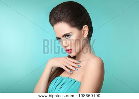 Matte lipstick. Closeup portrait beauty girl makeup. Manicured nails. Beautiful fashion woman brunette with eye shadow and pink lips isolated over turquoise background.