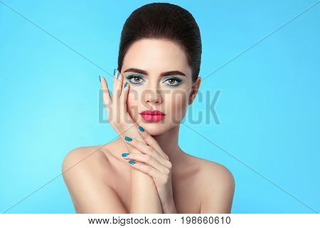 Closeup portrait beauty girl makeup. Manicured nails. Attractive young woman brunette with eye shadow and red matte lipstick isolated over blue background.