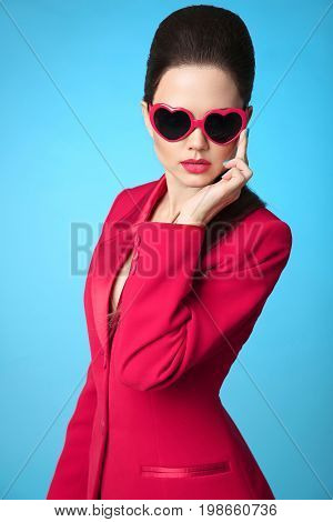 Fashionable trendy brunette wearing in heart sunglasses and red jacket isolated over blue studio background. Beauty fashion woman portrait.