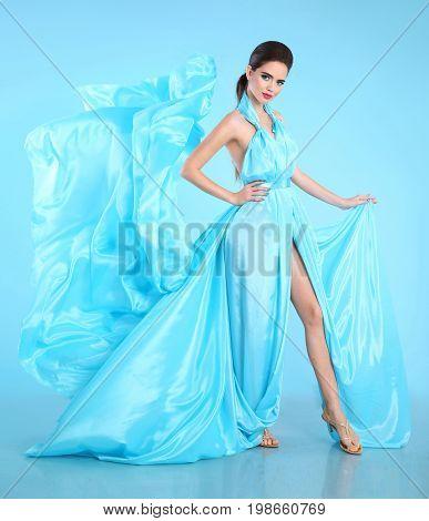 Fashion model in blue blowing chiffon dress. Glamour stunning Woman in long flying silk fabric waving on wind evening dress.