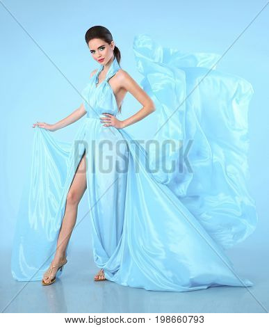Beautiful High fashion woman in blue dress posing in studio. Glamour model in blowing chiffon dress. Stunning Woman in long flying silk fabric waving on wind evening dress.