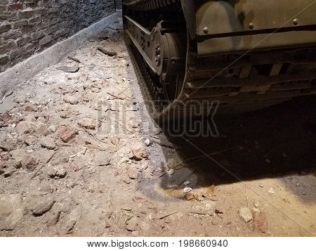 treads of old green tank on ground near red brick wall