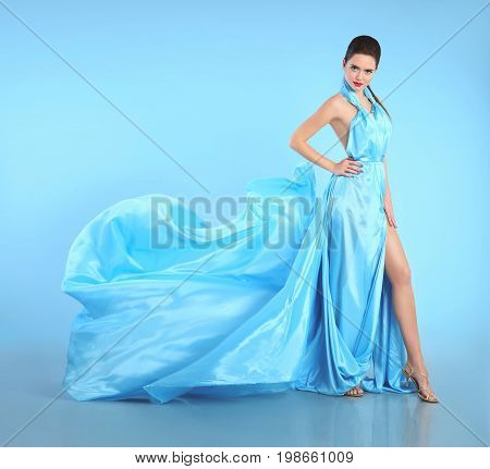 Beautiful Girl in blowing blue dress. Woman in Flying Gown, Silk Fabric Waving on Wind isolated on studio background.
