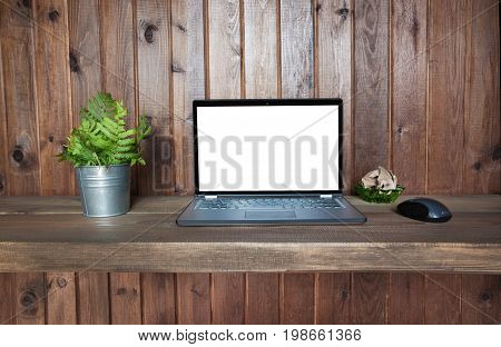 Workplace with open laptop with copy space on wooden desk for remote work in rustic style. Copy space.