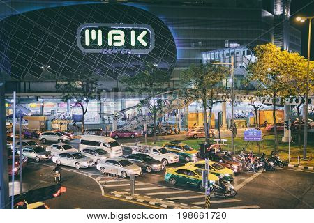 Bangkok, Thailand - January 31, 2016: MBK Shopping Center at night with typically heavy traffic on the roads. It is the most famous shopping mall and many tourists come to enjoy shopping here