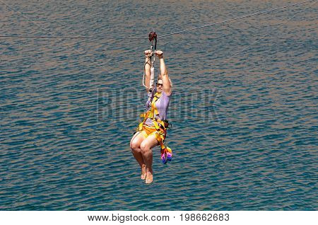 Ukraine Migea - July 30 2017: Zipline. The woman in the equipment slides on a steel cable. Trolley Track Over the lake. Extreme and active rest.