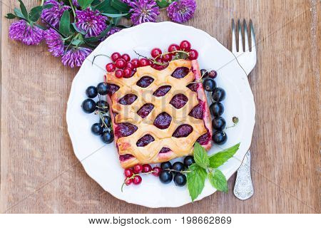 The Cake With Berry Jam Is Served With Red And Black Currants. Red Clover Flowers. Top View.