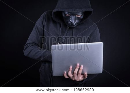 Anonymous male hacker using black mask to cover his face carrying laptop computer. Internet security and cyber attack concepts.