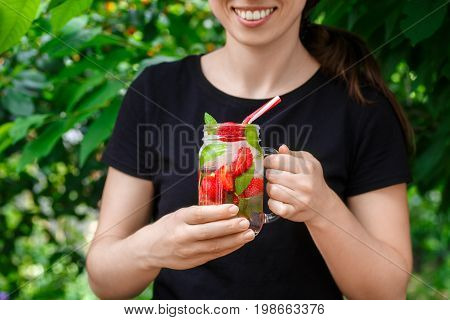 hand holding strawberry lemonade with ice and mint in mason jar outdoor. Glass jar of summer refreshing strawberry drink. Cold detox water with strawberry