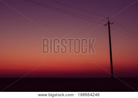 Single electric power pole on at sunrise, natural envirnomental clear energy background