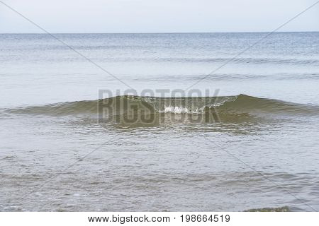 single wave formation above quiet sea waters