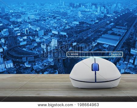 Search www button with wireless computer mouse on wooden table over city tower street and expressway Searching system and internet concept