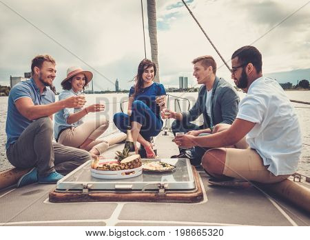Happy friends eating fruits and drinking on a yacht