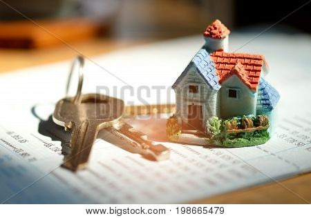 Home models and house key put on book bank,Concept money to buy a home.